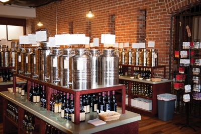 Self-serve canisters with many types of olive oil line the walls and counters at the Olive Tap.