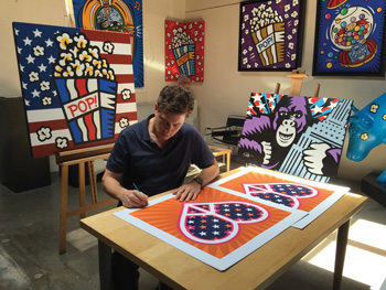 Burton Morris signing prints in his studio.