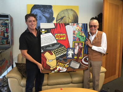 Burton Morris presents his finished portrait of Stan Lee to the late Marvel Comics mastermind in 2016.