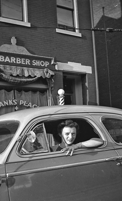 Virginia, Frank's wife, in a car in front of the shop, circa 1940s.